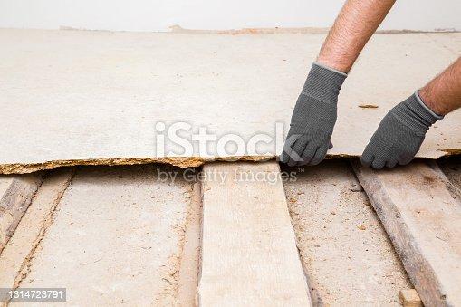 Young adult man hands in protective gloves breaking old wooden floor. Closeup. Preparing for repair work of home. Flooring change.