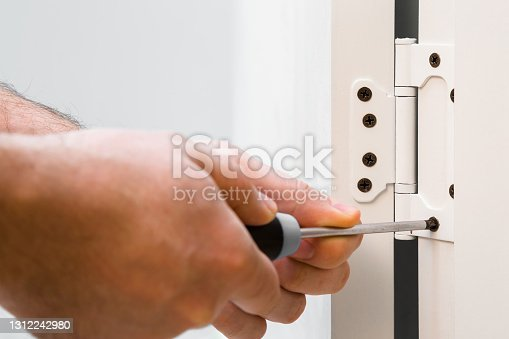 Young adult man hands using manual screwdriver and screwing hinges on white frame of wooden door in room. Closeup. Repair work of home. Renovation process.