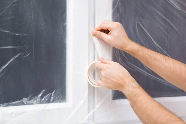 若い大人の男は、紙スコッチを使用して手を手にし、窓枠にプラスチックフィルムを接着します。クローズ アップ。家の修理作業の前に準備。 - 保護 テープ ストックフォトと画像