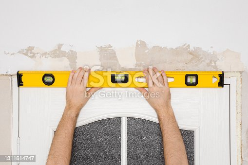Young adult man hands using yellow spirit level and measuring surface of new glass white wooden door. Closeup. Repair work of home. Renovation process. Front view.