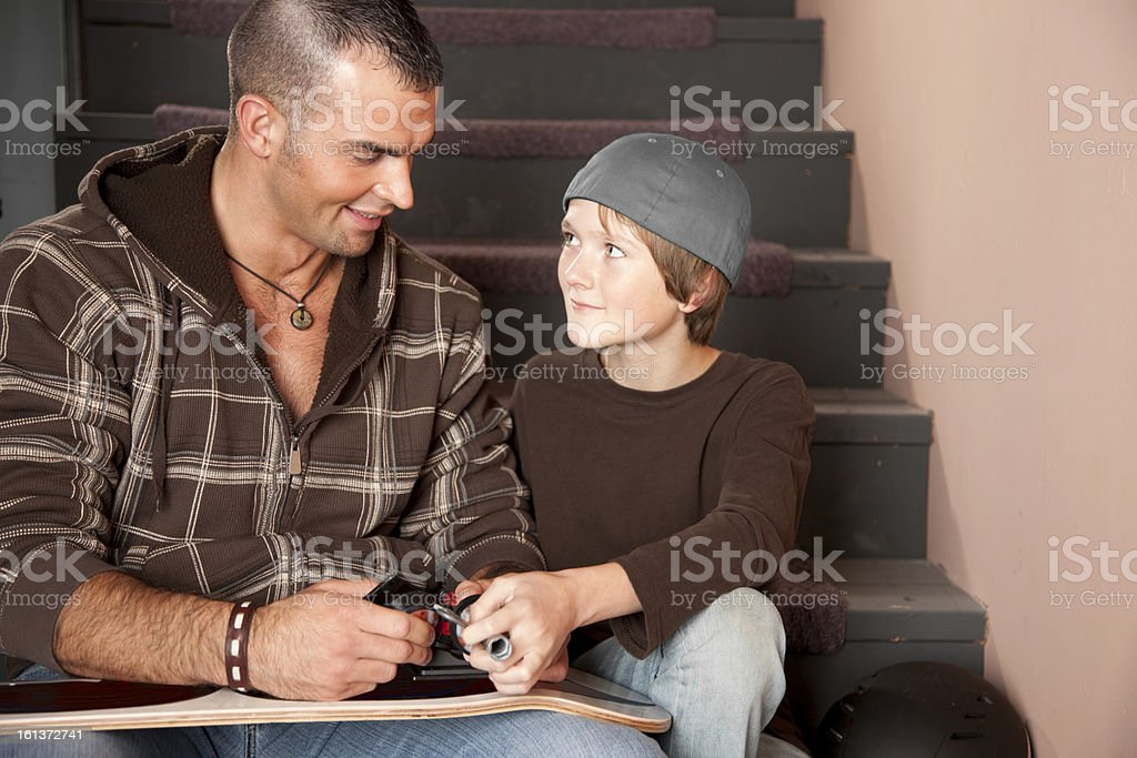 Young Adult Man Helping Adolescent Boy stock photo