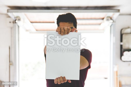istock Young Adult Man Holding White Paper 845966112