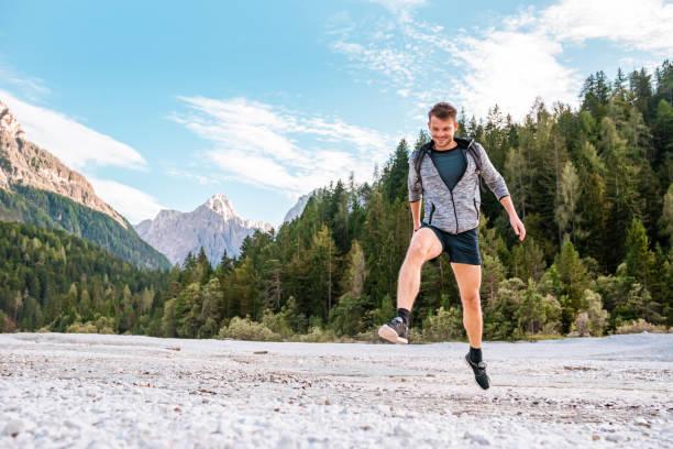 Junger erwachsener Mann springt über Pfützen in den Bergen Stockfoto – Foto