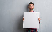 istock Young adult man over brick wall holding banner with a confident expression on smart face thinking serious 1042506388