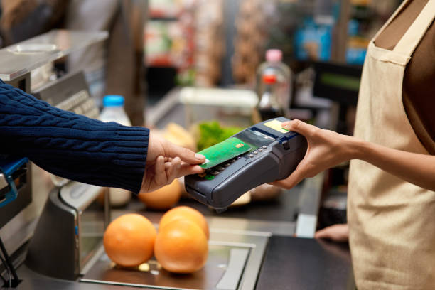 Young adult man paying for shopping in supermarket stock photo