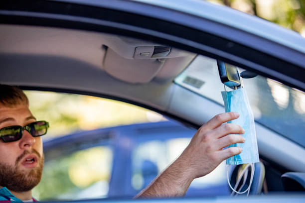jonge volwassen mens die beschermend gezichtsmasker op achter-meningspiegel in een auto hangt - mirror mask stockfoto's en -beelden