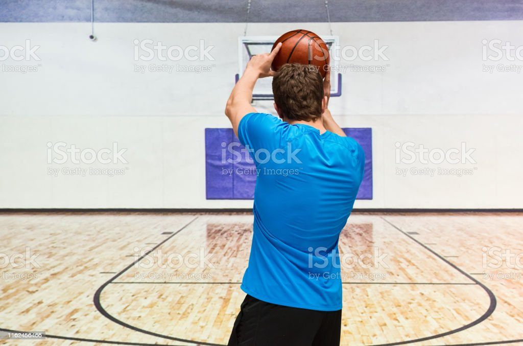 Young adult man playing baskertball at a sports court