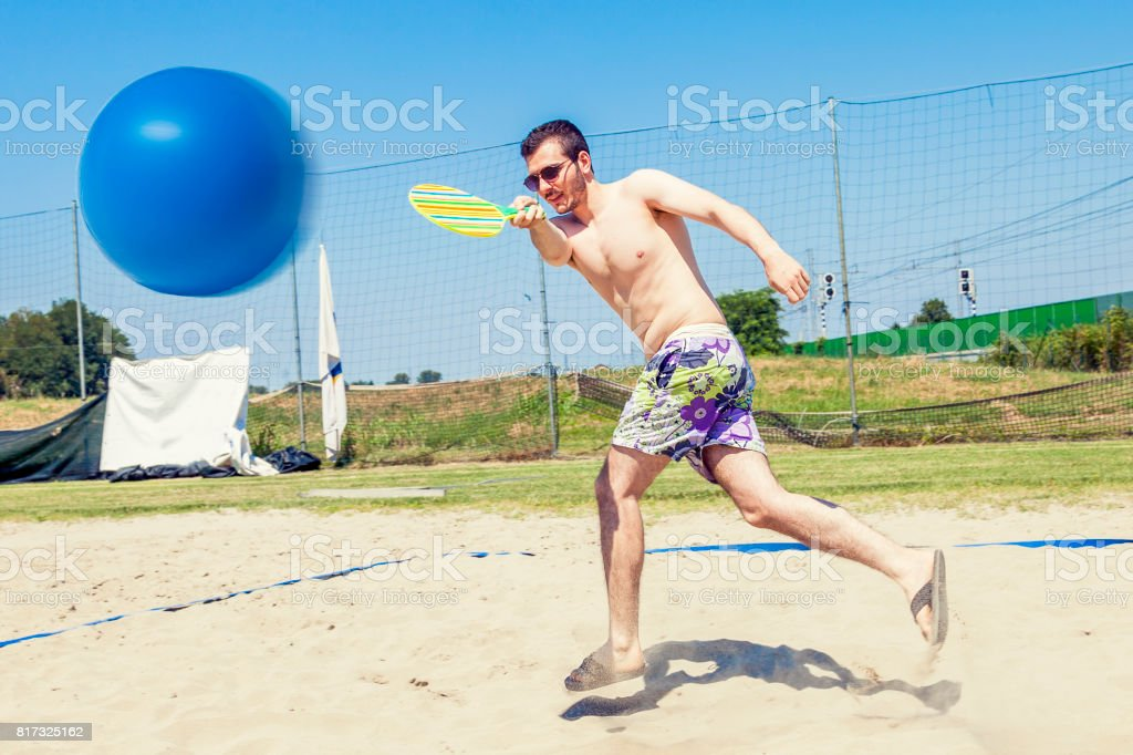 Young adult man plays tennis on the beach - foto stock