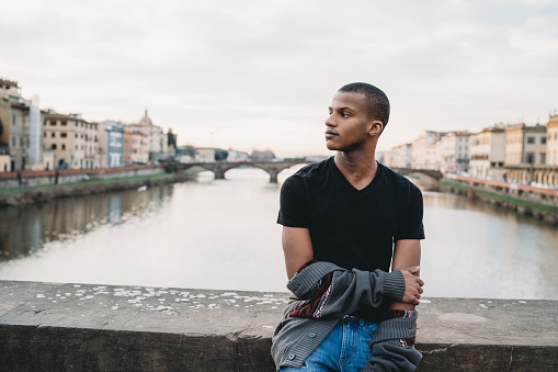 Young adult man portrait in the city during sunset against Arno River, Florence