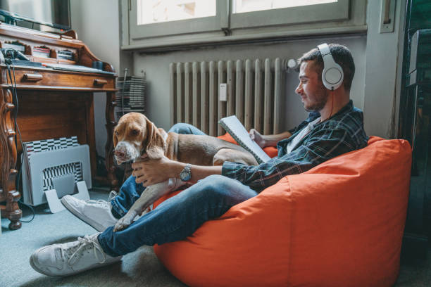 Young adult man reading and listening to music in his bedroom with his dog stock photo