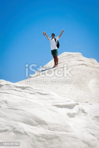 Young adult man rejoices on top of a white mountain. The photo is taken near the fantastic beach of Sarakiniko in Milos, Cyclades Islands, Greece. Concept of target achievement.