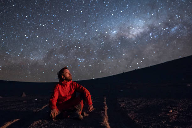 a young adult man seating and looking at the view of our milky way galactic core located in the constellation of sagittarius, an amazing view at atacama desert. chile - astronomy stock pictures, royalty-free photos & images