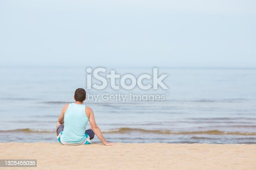 istock Young adult man sitting alone on sand and looking far away at sea beach in warm sunny summer day. Thinking about life. Empty place for emotional, inspirational text, quote or sayings. Back view. 1325455035