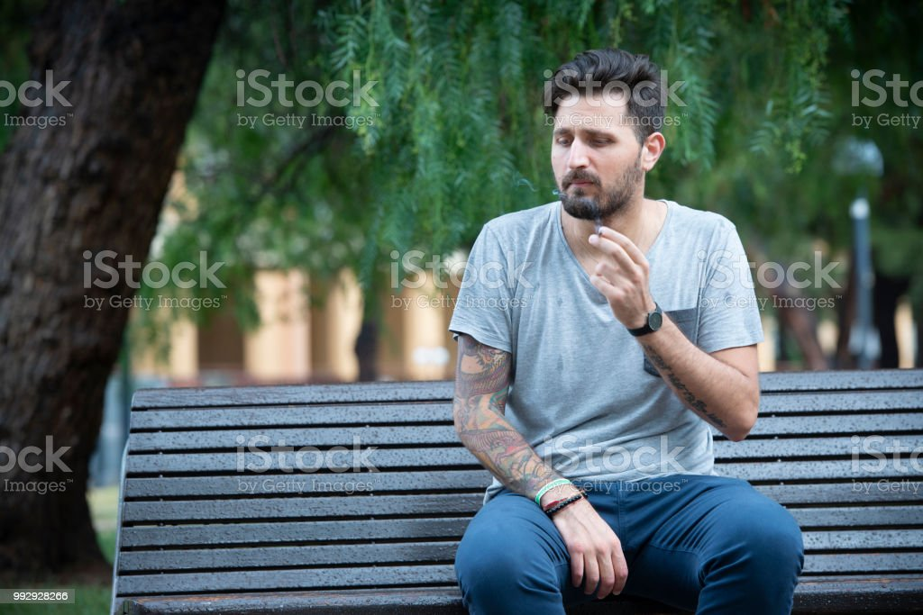 Young Adult Man sitting on a bench smoking a cigarette - foto stock