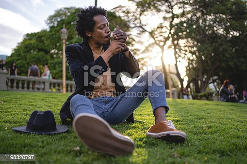 African American man sitting on a grass area and smoking a cigarette