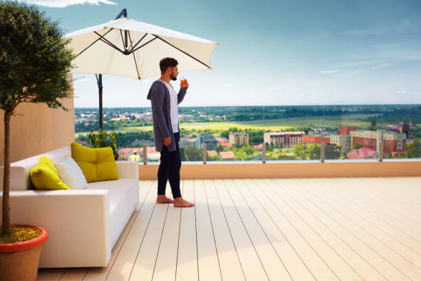 young adult man standing on rooftop terrace, enjoying beautiful cityscape view stock photo