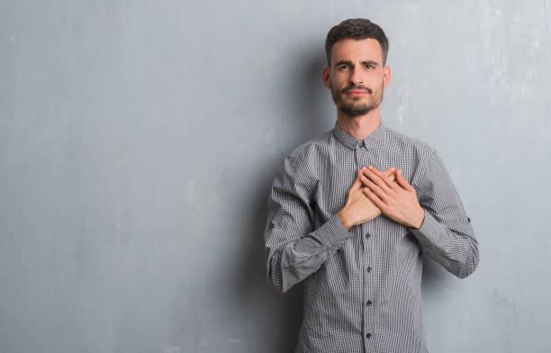 junger erwachsenen mann stehend über graue grunge wand lächelnd mit händen auf brust mit geschlossenen augen und dankbar geste auf gesicht. gesundheitskonzept. - die wahrheit tut weh stock-fotos und bilder