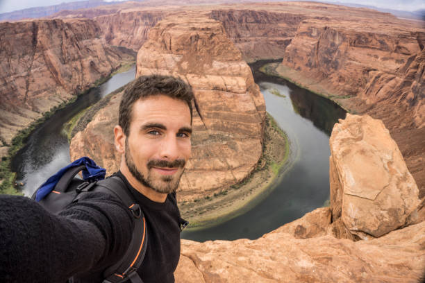 Young adult man taking a selfie at the Horseshoe Bend A young happy traveler taking a selfie. Horseshoe Bend on the Background. Page, Arizona horseshoe bend colorado river stock pictures, royalty-free photos & images
