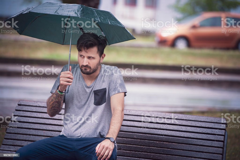 Young Adult Man Waiting for Someone Under The Rain sitting in the...