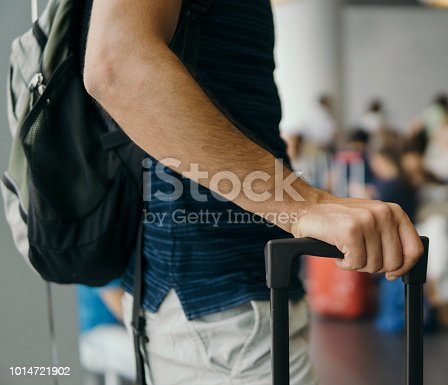 Man with trolley waiting for the plane at the terminal during his casual business trip.