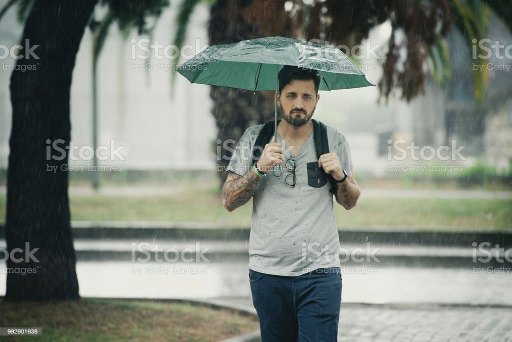 Young Adult Man Walking Under The Rain - foto stock