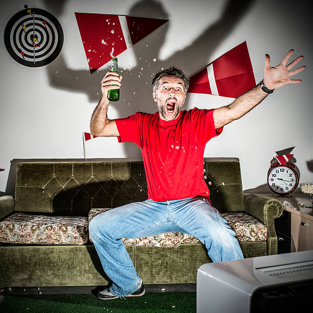 Young adult man watching football on television: Goal! Young adult man watching football on television: Goal! man cave couch stock pictures, royalty-free photos & images