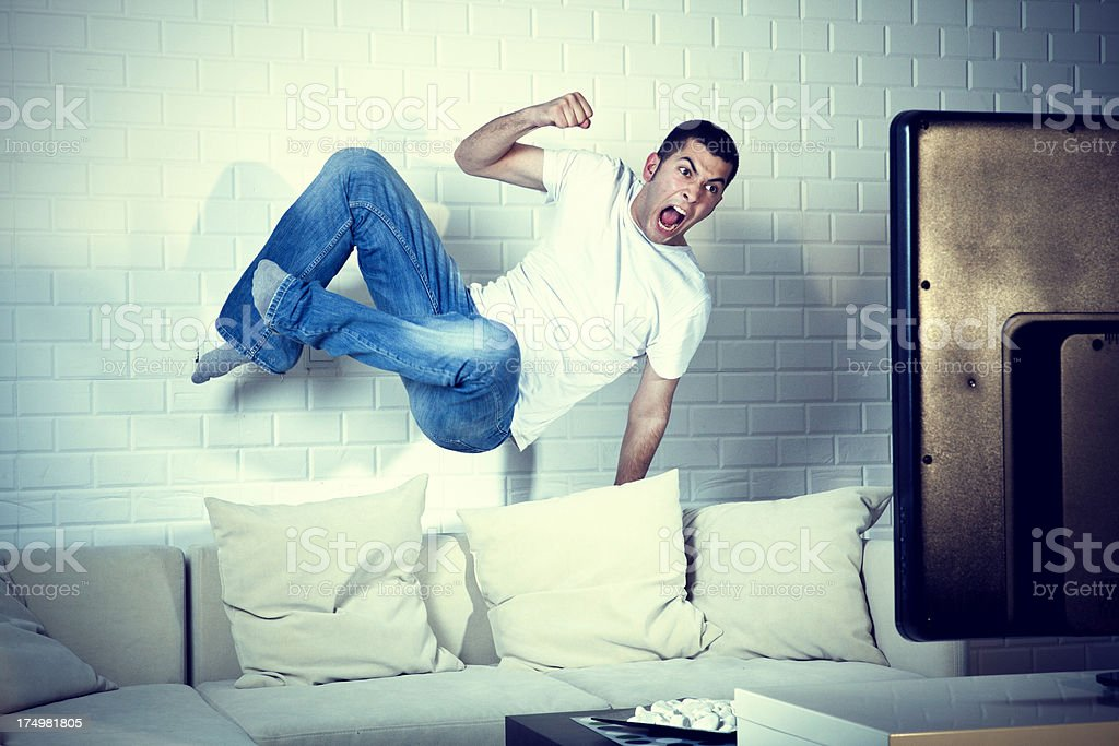Young adult man watching football on television: Goal! stock photo