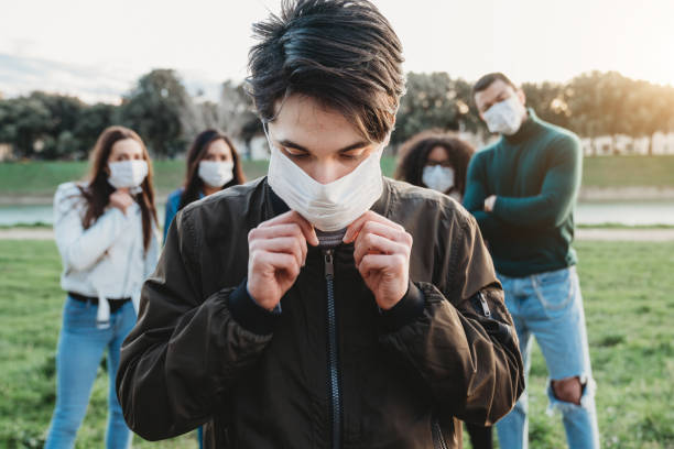 Young adult man wearing a pollution mask to protect himself from viruses. His friends are in the background. stock photo