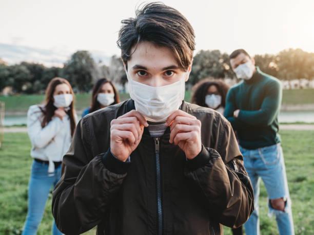 junger erwachsener mann trägt eine verschmutzungsmaske, um sich vor viren zu schützen. seine freunde sind im hintergrund. - jugendalter stock-fotos und bilder