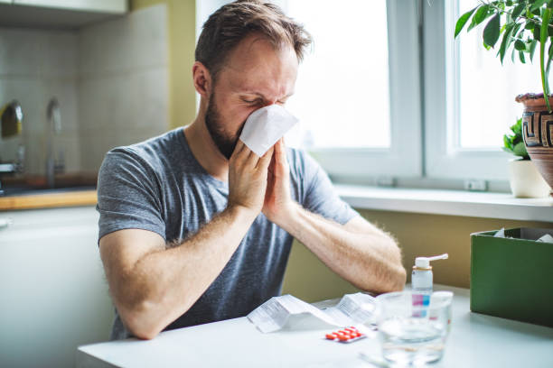 Young adult man with cold , flu, running nose stock photo