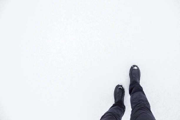 Young, adult man's legs in black boots walking on white, fresh snow. Enjoying stroll. Footwear for daily walking in winter season. Empty place for text, quote or sayings. Point of view shot. Young, adult man's legs in black boots walking on white, fresh snow. Enjoying stroll. Footwear for daily walking in winter season. Empty place for text, quote or sayings. Point of view shot. single step stock pictures, royalty-free photos & images