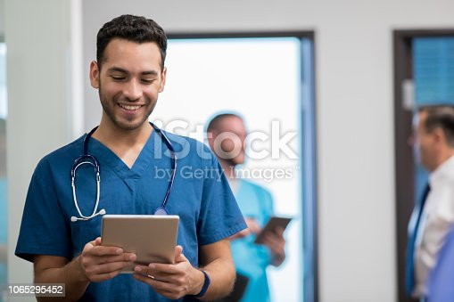 Young adult Hispanic man is medical student or resident. He is walking down hallway in hospital and is holding a digital tablet. Man wearing scrubs and a stethoscope.