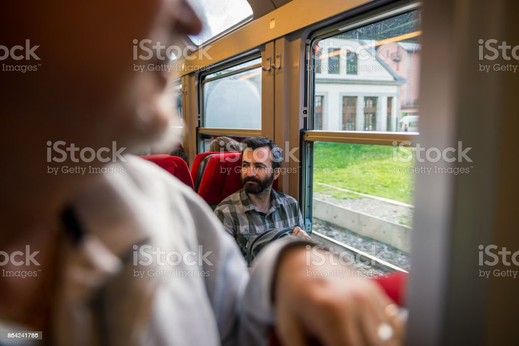 Young adult men commuter traveling by train seated in sunny summer day royalty-free stock photo