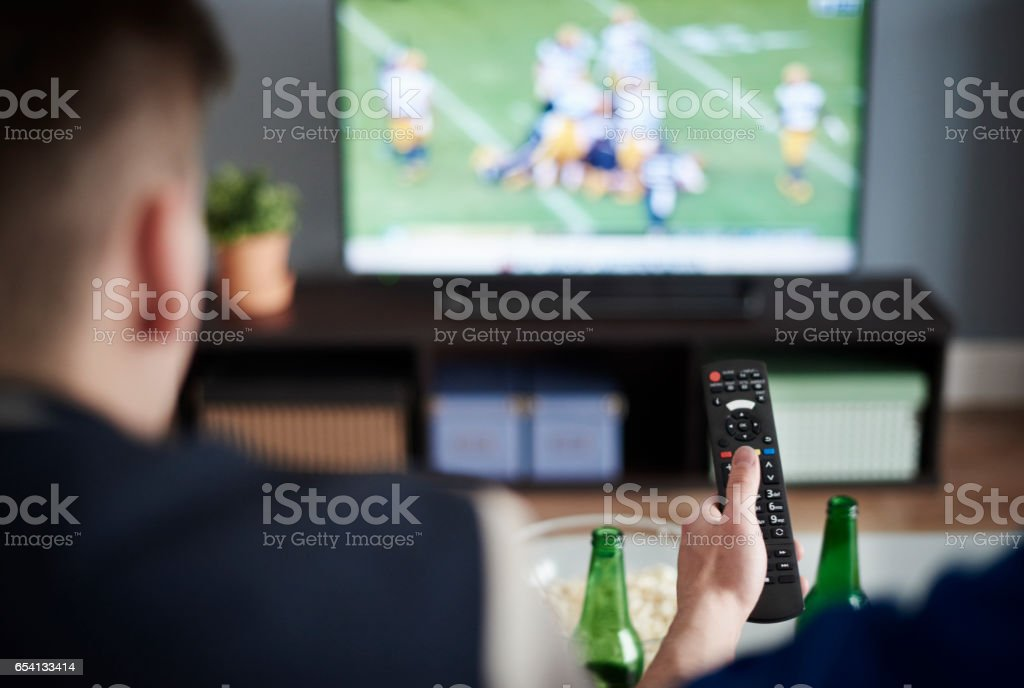 Young adult men friends watching American football stock photo