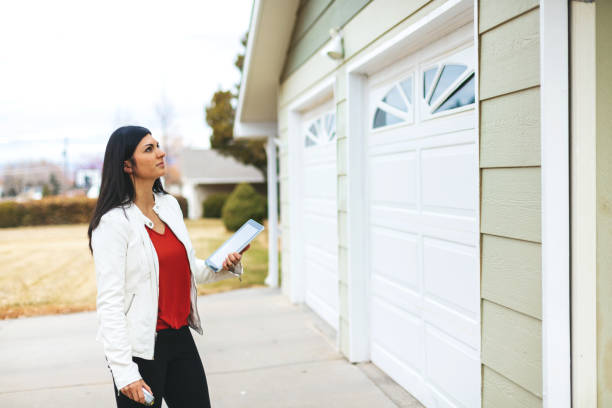 Young Adult Millennial Female Appraiser Measuring Home Features and Assessing Value in Western Colorado stock photo