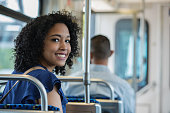 Young adult mixed race woman looks at the camera and smiles while riding a commuter train.  She is dressed professionally and sitting down.