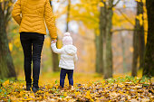 Young adult mother and little daughter walking on yellow fallen leaves in forest. Golden autumn. Spending time together in beautiful day. Enjoying peaceful stroll. Back view.