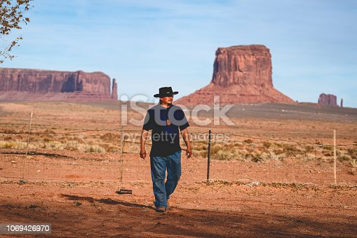 Handsome and rugged traditional Navajo Man portrait outside in Monument Valley Arizona with scenery view