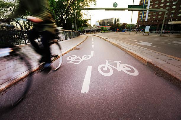 junger erwachsener auf fahrrad in der stadt - fahrradwege stock-fotos und bilder