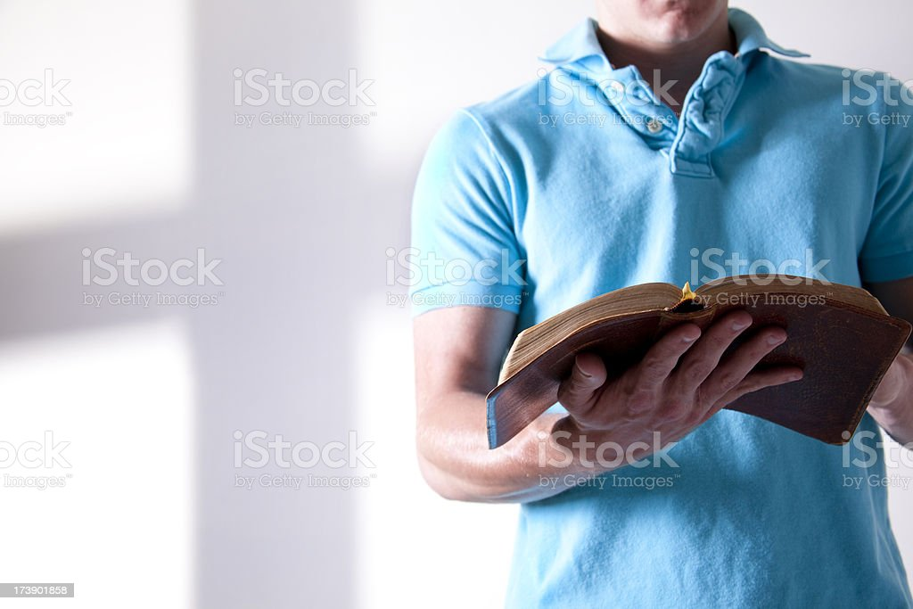 Young adult, open Christian Bible hands. Cross shadow on wall. royalty-free stock photo
