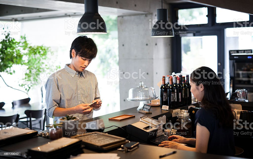 Young adult paying at a restaurant stock photo