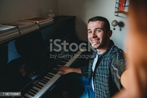 Young adult pianist taking a selfie at home