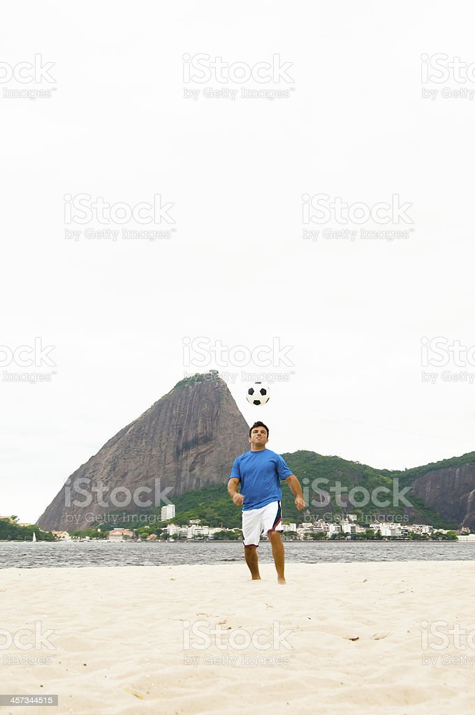 Young Adult Playing Football on Praia do Flamengo Beach stock photo