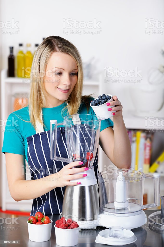 Young Adult Pouring Blueberries In A Food Processor royalty-free stock photo