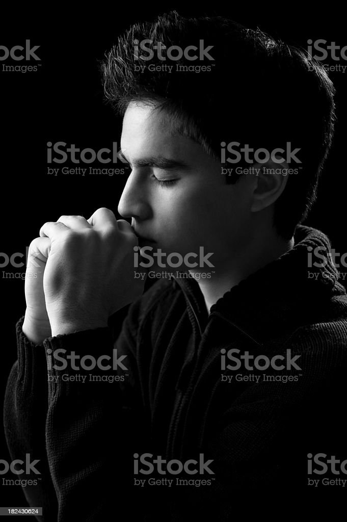 Young adult praying b&w royalty-free stock photo