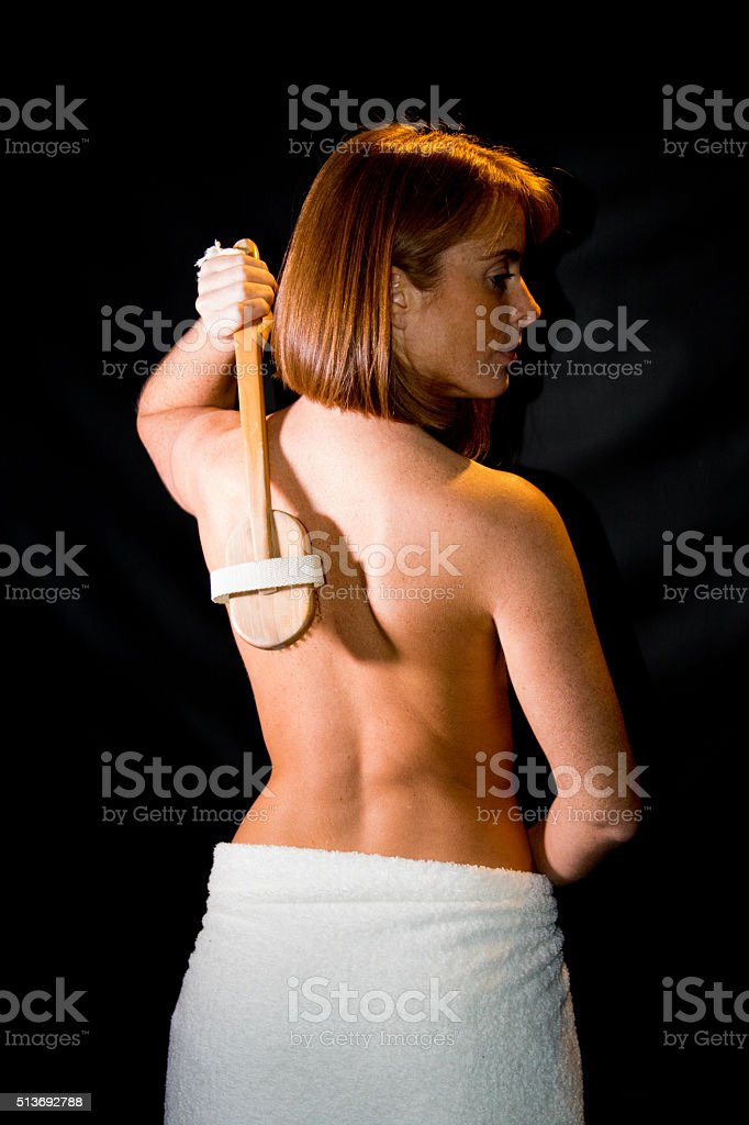 Young Adult Scrubbing Her Back stock photo