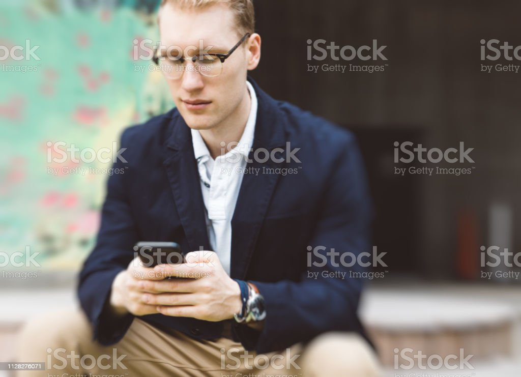 young adult sitting outdoors texting stock photo