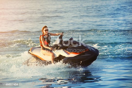 Young adult sporty caucasian woman riding jet ski in ocean blue water at warm evening sunset. Beach extreme sport activities and recreation.