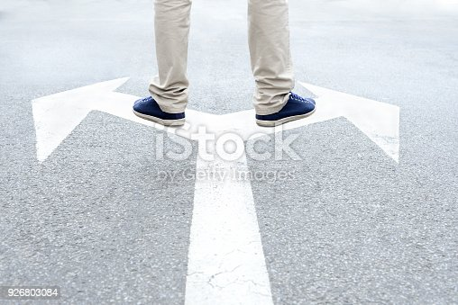 istock Young adult standing on arrows to make decision 926803084