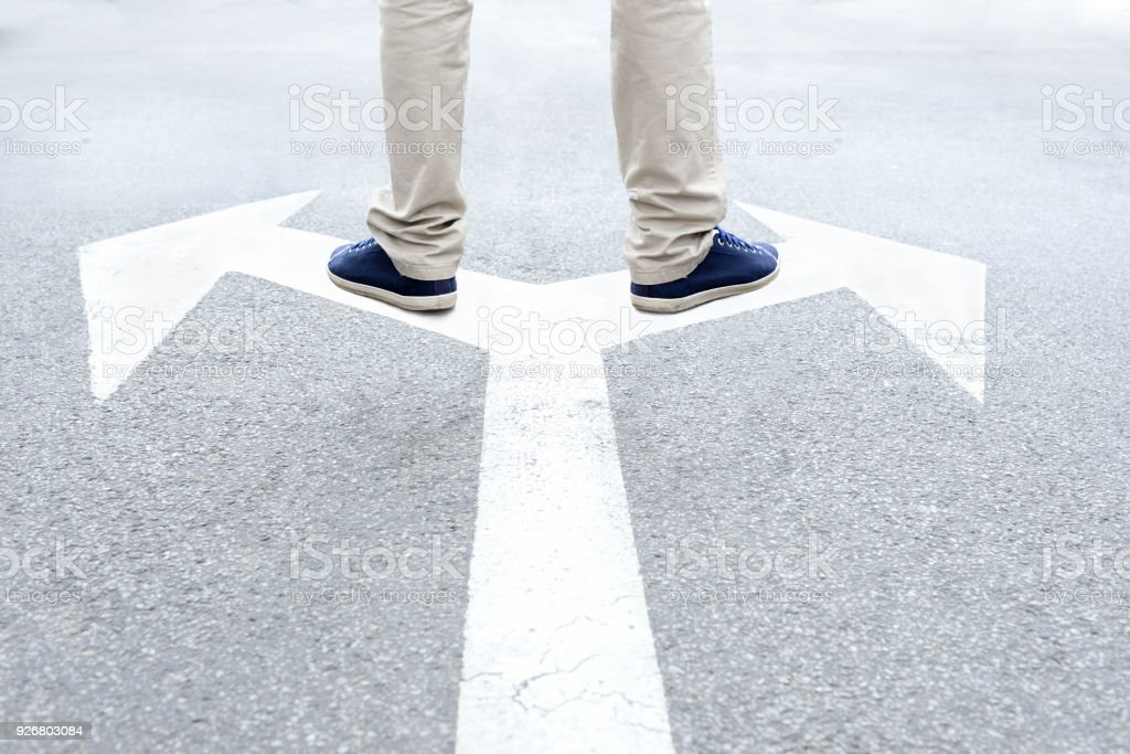 Young adult standing on arrows to make decision - foto stock